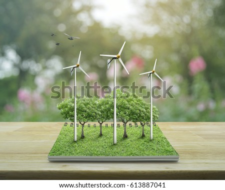 Wind turbines, trees, grass and birds from an open book on wooden table over blur pink flower and garden, Ecological concept #613887041