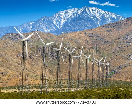 Wind turbines with a scenic snow-capped mountain in the background and a clear blue sky