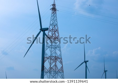 Wind turbines with high voltage pole on the mountain, Wind turbines produce electricity with a view of the countryside. #1391139641
