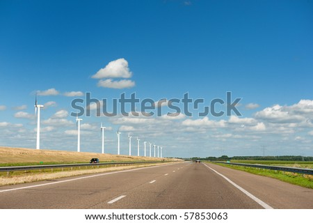 Wind turbines with highway and cars in summer