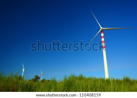 Wind turbins producing aeolian energy under blue sky on a green field of Calabria. The sky is enhanced with a polarizer filter
