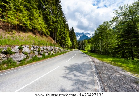 Winding asphalt road in Austrian landscape with forests, fields, pastures and meadows #1425427133