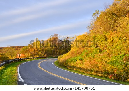 Winding asphalt road with autumn foliage