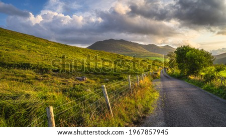 Winding country road leading toward highest mountain in Ireland, Carrauntoohil in MacGillycuddys Reeks mountains at sunset, Ring of Kerry, Ireland Stok fotoğraf ©