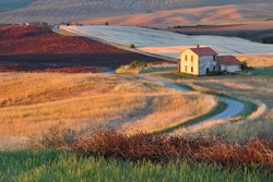 Winding country road with farm house and cultivated grain fields