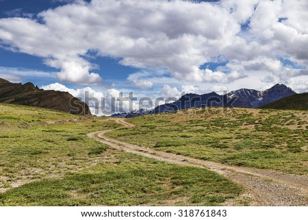Winding dirt road among green meadows going to snow peaks