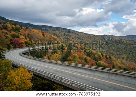 Winding, elevated roadway through the mountains during autumn