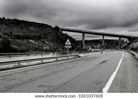Winding expressway with separation barrier in Spain. The Ice Likely sign in the warning triangle. Intersection of two spanish highways. Black and white picture