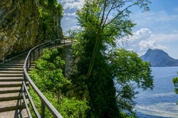 Winding hiking path with stone steps and metal railing along a steep rock wall. Part of the
