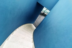 Winding metal staircase and blue wall