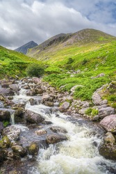 Winding mountain stream or river in Cronins Yard. Green valley with Carrauntoohil in a distance, the highest mountain in Ireland, Ring of Kerry