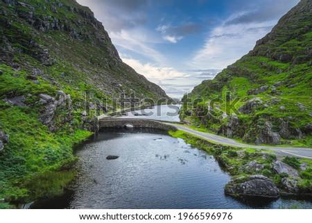 Winding narrow road crossing stone Wishing Bridge in Gap of Dunloe, Black Valley, MacGillycuddys Reeks mountains, Ring of Kerry, Ireland Stok fotoğraf ©