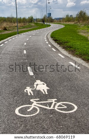 Winding pedestrian road for walkers and bicycles, mother with child and bike sign on the road