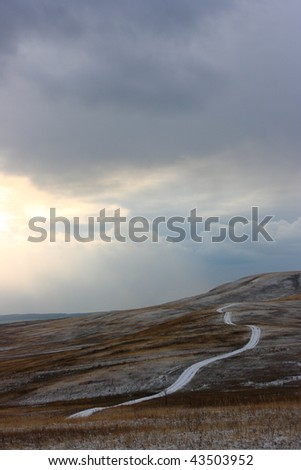 Winding road across the steppe hills in the late autumn