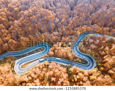 Winding road from high mountain pass, in autumn season. Aerial view by drone . Romania  #1210885378