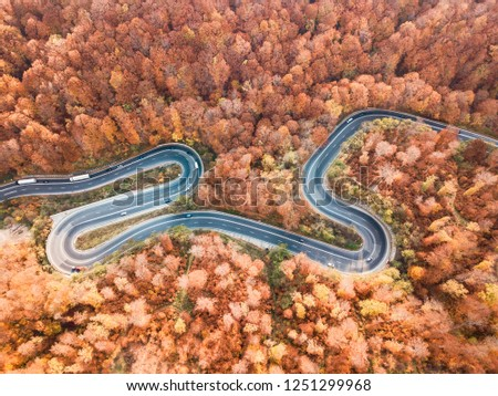 Winding road from high mountain pass, in autumn season. Aerial view by drone. Romania  #1251299968