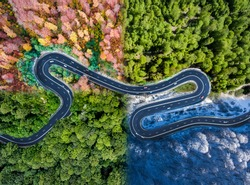 Winding road in all four seasons. Aerial view of a curved highway trough the forest. Composite drone roadway weather image of a hairpin turn