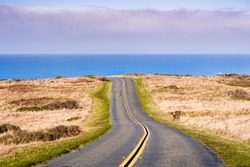 Winding road on the Pacific Ocean coastline on a clear sunny day, Point Reyes National Seashore, California