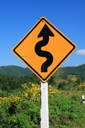 winding road sign in yellow and black on blue sky background