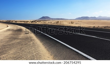 Winding road through the dunes of Corralejo desert with volcano in the background, in Fuerteventura, Canary Islands, Spain.