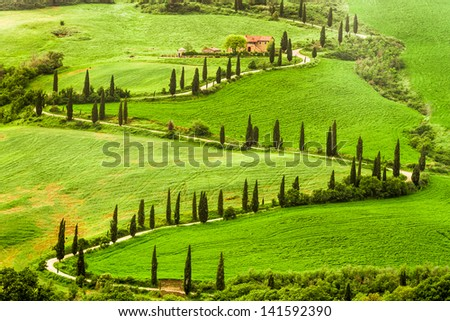 Winding road to agritourism in Italy on the hill - stock photo