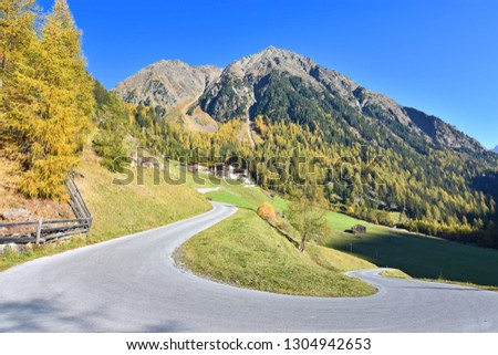 Winding road towards the small hamlet Winnebach near the Oetztal valley in the Stubai Alps (Tyrol, Austria). The houses are surrounded by colorful autumn forest and rocky mountains under blue sky. #1304942653