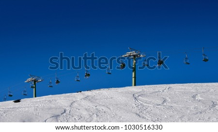 Winding snowboard trace and chairlift shadow on white snow - winter sports concept #1030516330