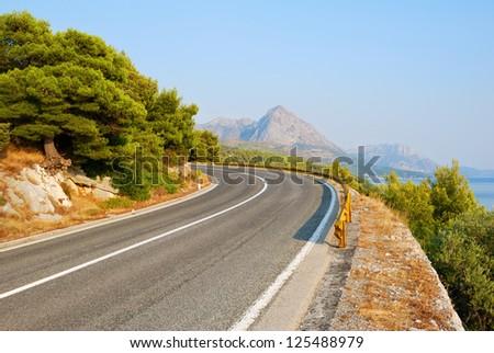 Winding Tarmac Road above blue sea - stock photo