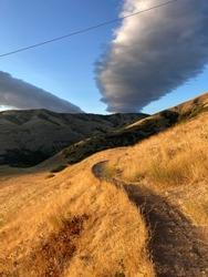 Winding trail on beautiful grassy mountainside with unique clouds