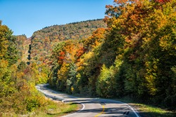 Winding turning curve highway road in Snowshoe town, Allegheny mountain ski resort village of West Virginia in colorful autumn fall with maple trees foliage