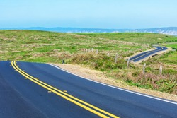 Winding two lane road on scenic Pacific Ocean coastline on a clear sunny day at Point Reyes National Seashore, California