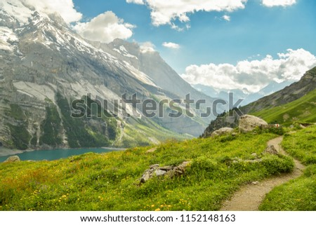 Winding walking trail high above the Oeschinensee lake with picturesque panorama of Swiss Alps #1152148163