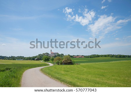 winding way to andechs cloister in idyllic rural bavarian landscape, blue sky with clouds #570777043