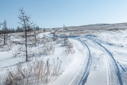 Winding winter road in the snow-covered steppe