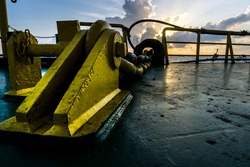 Windlass anchor chain stopper at bow of a construction work barge during sunset at oil field