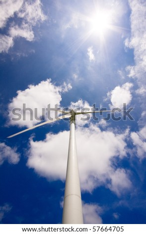 Windmill against a blue sky and clouds, alternative energy source