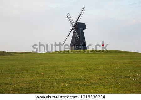 Windmill and red flag with green lawn and overcast sky in Rottingdean Windmill golf course. East Sussex, England.