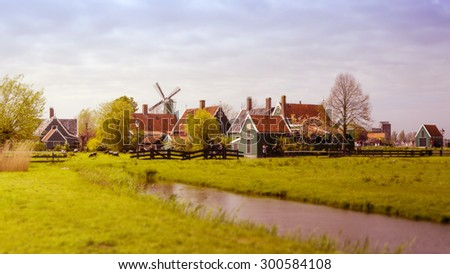 Windmill and rural houses in Zaanse Schans, The Netherlands. Tilt-shift effect and Color filter effect.