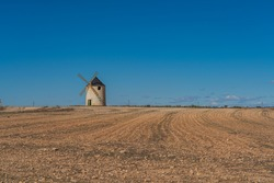 Windmill at the Don Quixote route in Spain on a sandy field