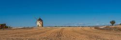 Windmill at the Don Quixote route in Spain on a sandy field, panorama view