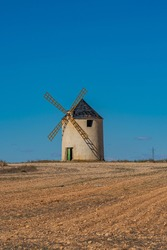 Windmill at the Don Quixote route in Spain on a sandy field, vertical