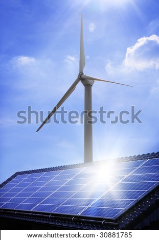 windmill behind a solar panel on a roof - stock photo