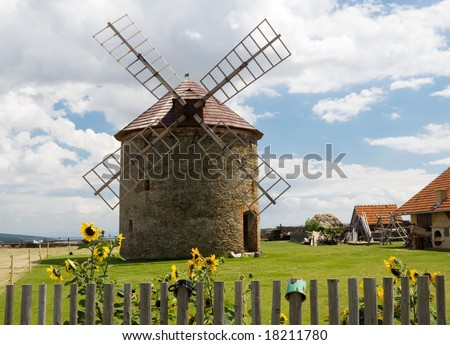 Windmill behind a wood stockade with cup and sunflowers