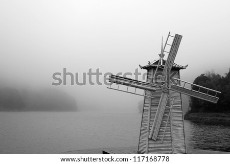 Windmill beside river in the coming fog