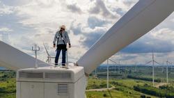 Windmill engineer wearing PPE standing on wind turbine