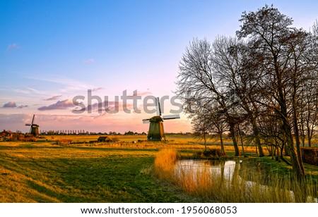 Windmill farm at dawn in Holland. Sunrise windmill farm scene. Windmill at dawn