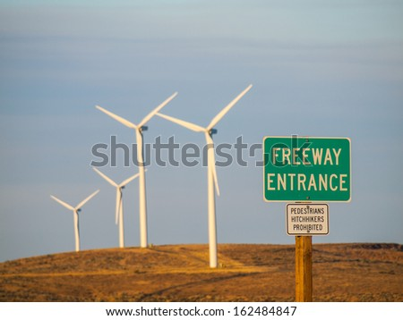 Windmill Farm on a Mountain with Freeway Entrance Signs at Dusk