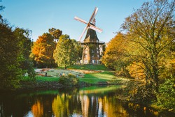 Windmill in a park with many trees and a river. Very colorful po