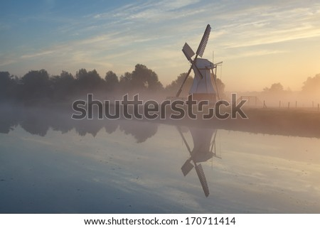 Stock Photo windmill in morning sunshine reflected in river, Holland