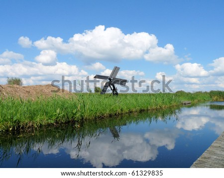 Windmill in reed field with clouds reflected in the water